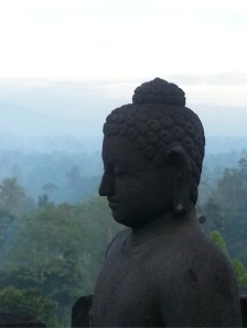 Sunlight reflects off of the mist behind this statue of the buddha